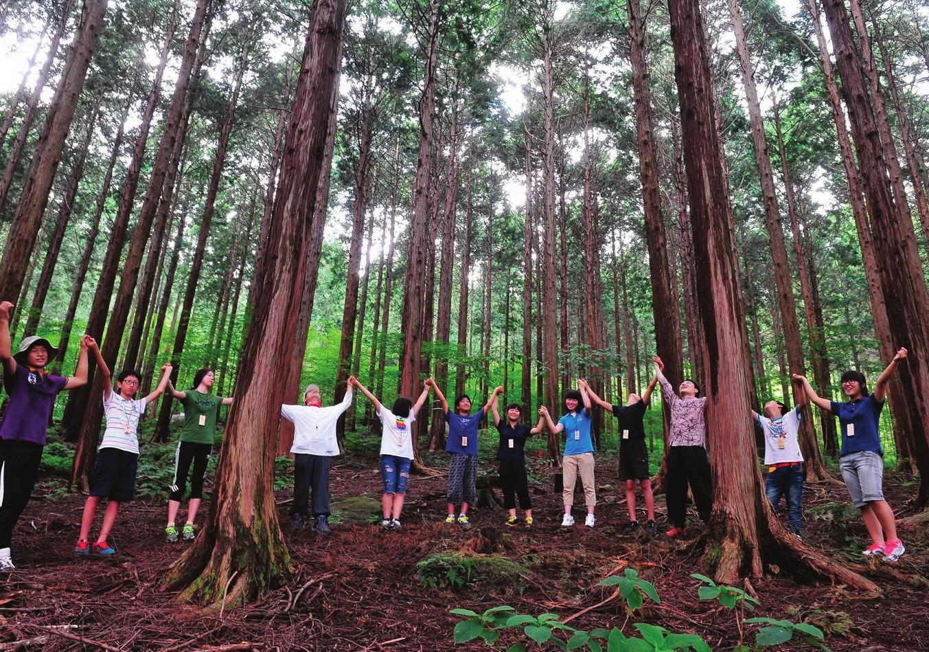 Students soak up the fragrance from retinispora trees in a local forest.