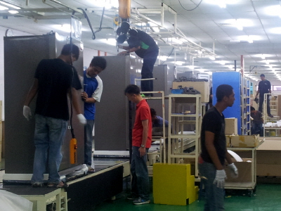 Workers produce refrigerators in Dongbu Daewoo Electronics' plant in Malaysia.