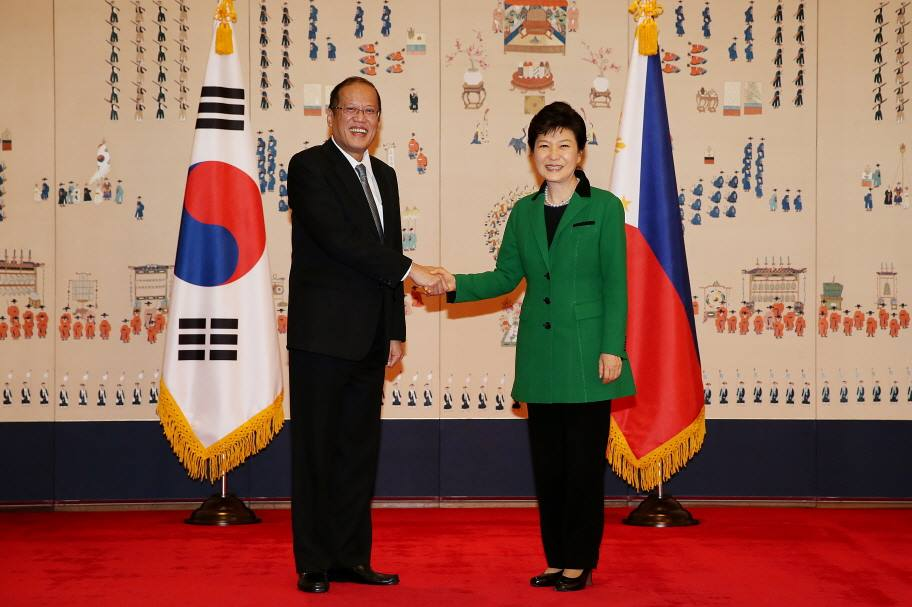 South Korean President Park Geun-hye and Philippine President Benigno Aquino III shake hands ahead of a summit in Seoul on October 17.