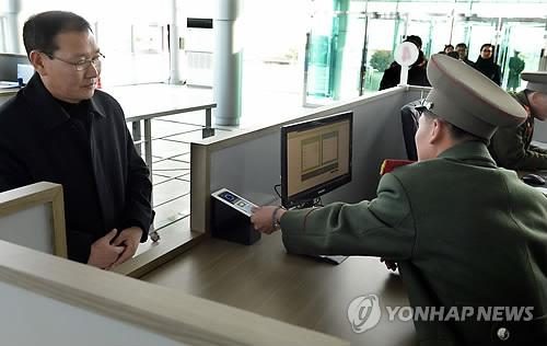 A North Korean official checks a South Korean visitor to the Kaesong Industrial Complex with the newly-built radio frequency identification system at an immigration office on Jan. 28, 2014. (Press corps-Yonhap)