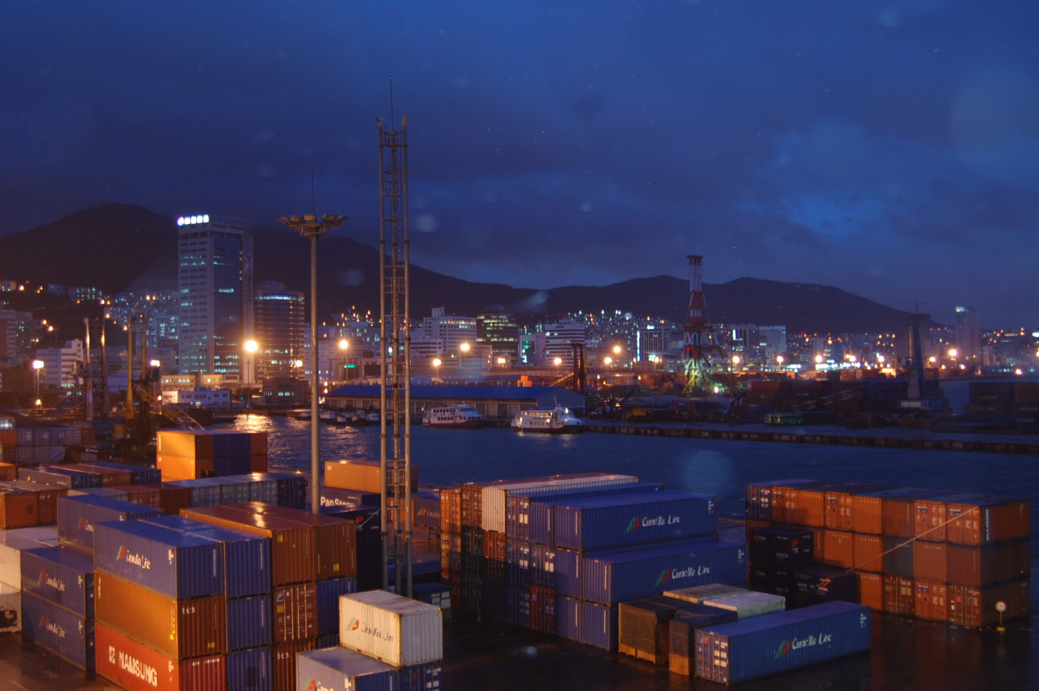 Dusk falls over cargo containers stacked 3-high at Busan Harbour Cargo Terminal. Imports and exports constitute 33.7% of the total national economy. (Photo by Eastberliner via Wikimedia Commons)