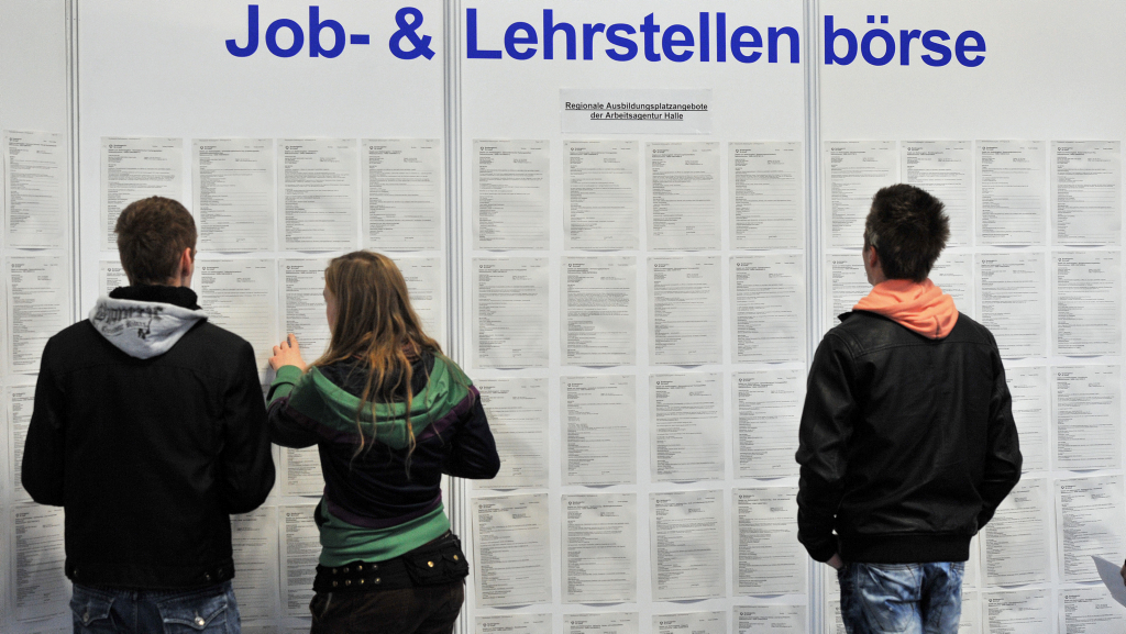 Out-of-work Germans look over a job posting board.