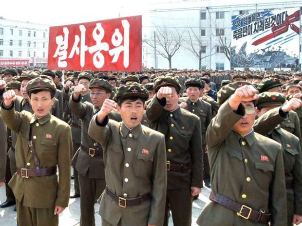 "North Korean soldiers pledge their allegiance under the banner that says ""guarding the leadership with life."""