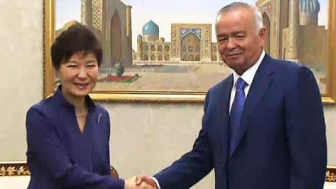 President Park Geun-hye shakes hands with President Islam Karimov of Uzbekistan after her arrival at the Tashkent International Airport on June 16.