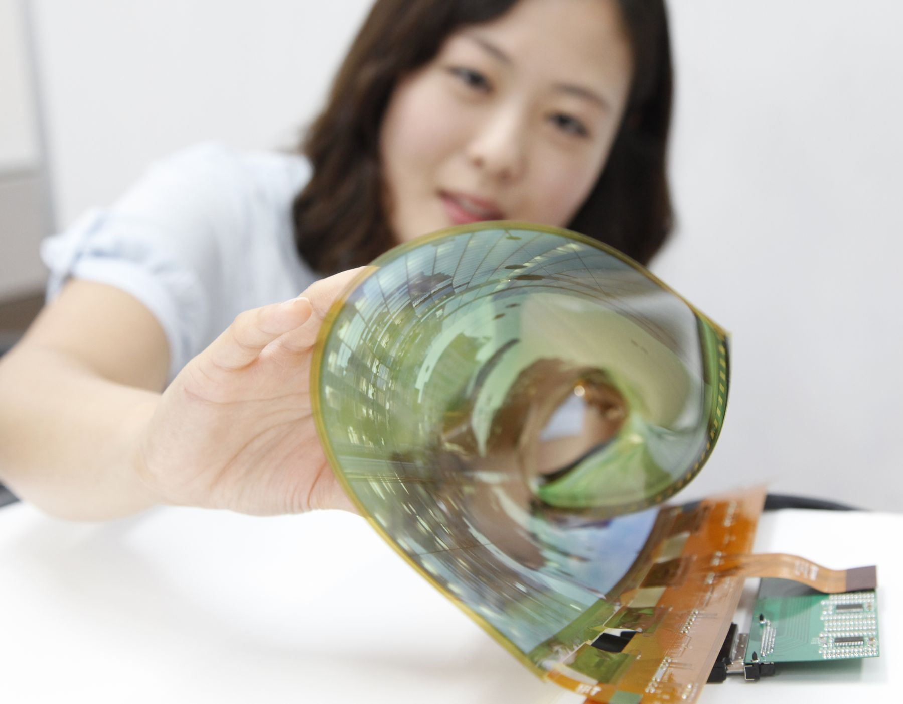 An LG Display employee is rolling up an 18 in. flexible OLED display with a 30R radius of curvature that could be used for a rolled-up TV.
