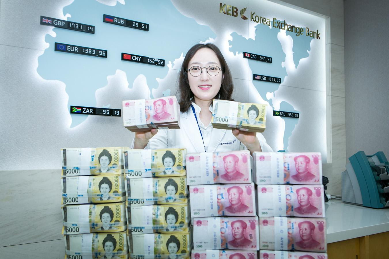 A bank employee displays both Korean won (left) and Chinese yuan (right). (Photo via Korea Exchange Bank)