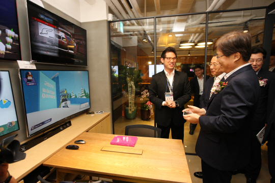 Choi Yang-hee (right), minister of Science, ICT and Future Planning, demonstrates smart media at the opening ceremony of the Smart Media Innovation Center held in the Korea Communications Agency in Seoul on July 31.