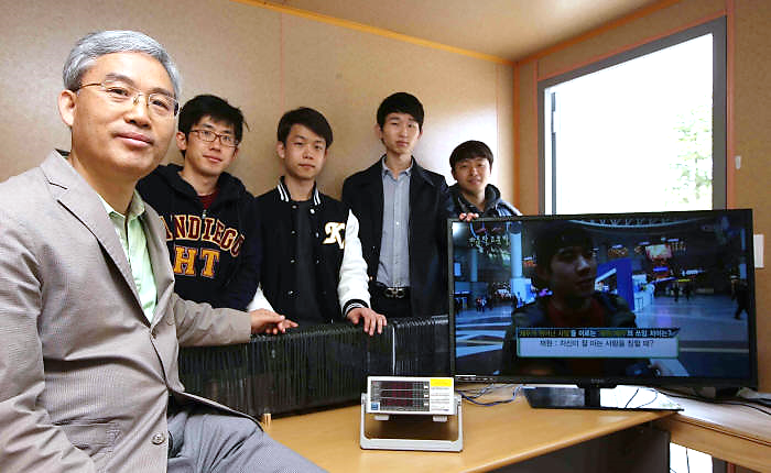A research team led by Professor Rim Chun-taek at KAIST (left) operates an LED TV using a new wireless power transmission tech.