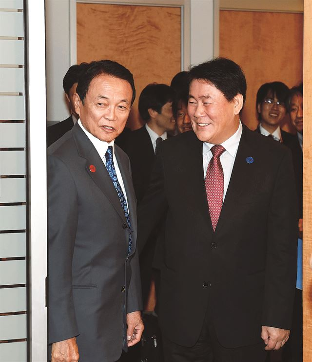 Deputy Prime Minister and Minister of Strategy and Finance Choi Kyung-hwan (right) speaks with Taro Aso, deputy prime minister and minister of Finance in Japan, at the annual general meetings of the IMF and World Bank held in Washington D.C.
