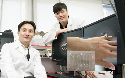 UNIST Professor Park Jang-woong (right) and the transparent electronic tattoo (inset) he developed with other researchers.