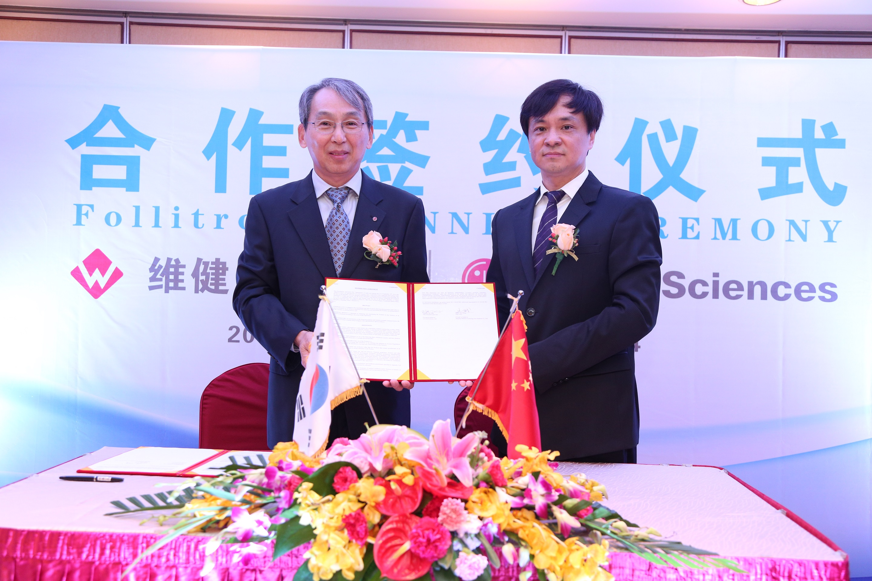 LG Life Sciences CEO Jung Il-jae (left) poses with a Weijian Pharma Group representative after signing an exclusive sales contract.