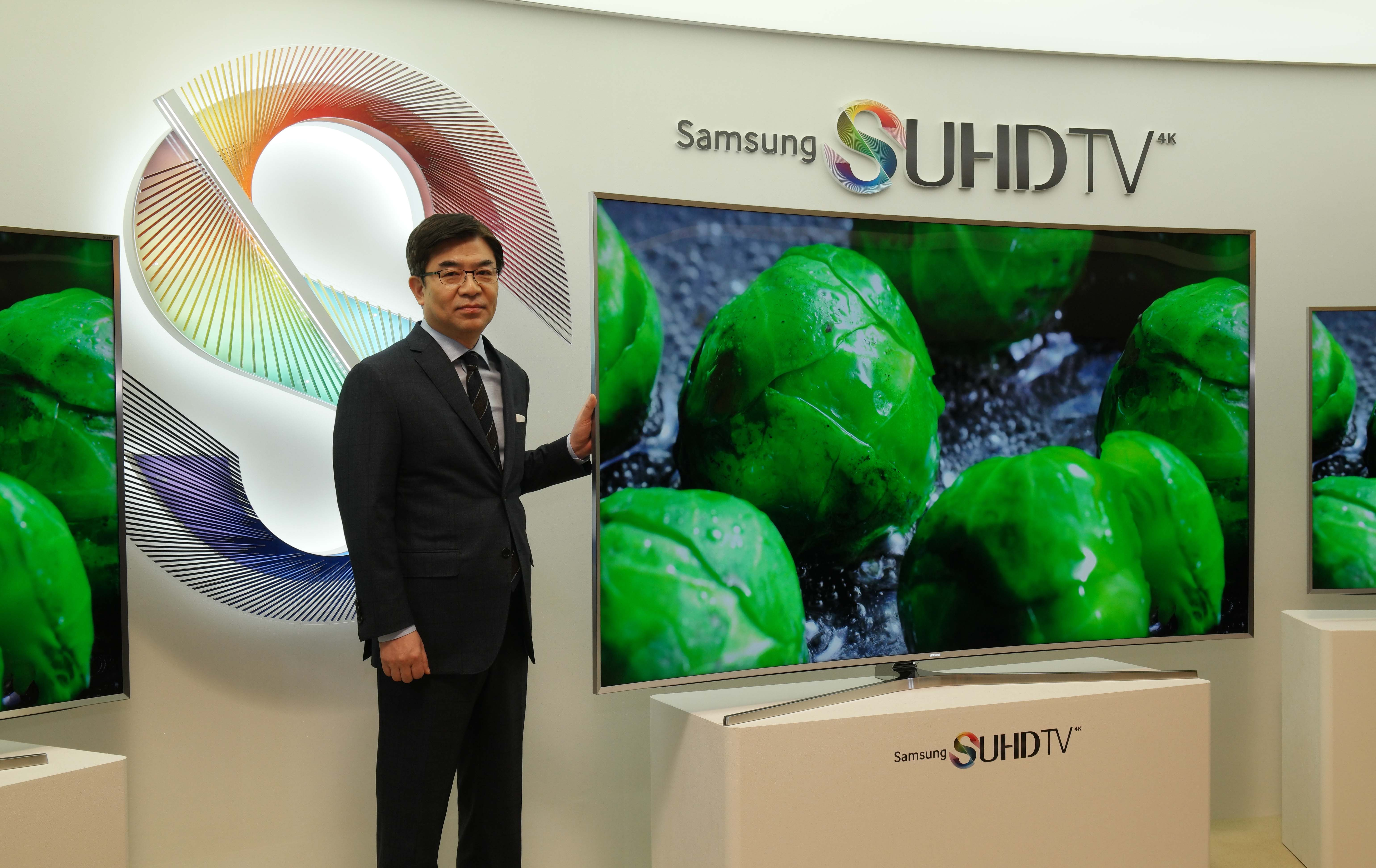 Kim Hyun-suk, president of the V business at Samsung Electronics, stands next to a Samsung SUHD TV.