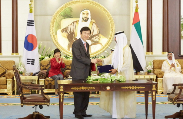 A South Korean minister shakes hands after inking a Memorandum of Understanding with Abu Dhabi Investment Company, a state fund owned by the United Arab Emirates, in Abu Dhabi.