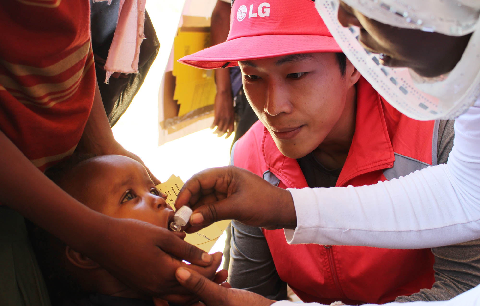 An Ethiopian child receives an experimental cholera vaccine from a local nurse while LG staff supervise.