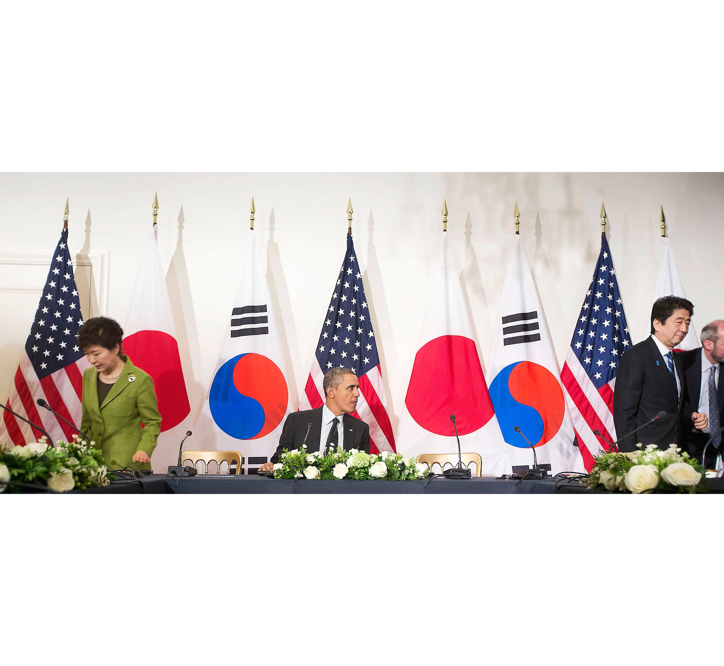 Korean President Park Geun-hye and Japanese Prime Minister Shinzo Abe leave U.S. President Barack Obama from opposite sides of the table after a photo opportunity at a nuclear summit at The Hague on March 25.