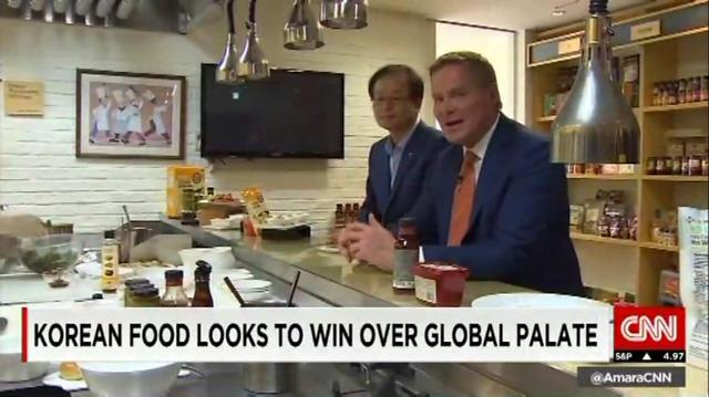 Kim Chul-ha (left), CEO of CJ CheilJedang, introduces his company's Korean food products to Michael Holmes (right), a CNN anchor.