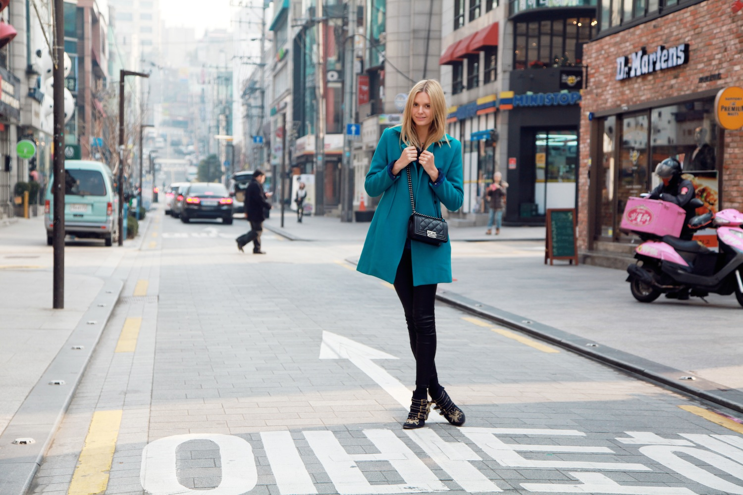 A model poses on a street in Gangnam.
