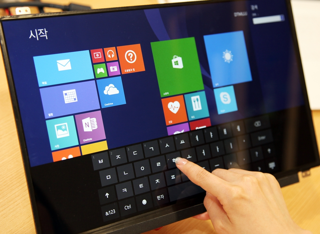 "The hand of an LG Display employee tests Microsoft's Windows operating system on the new ""in-cell"" touch lightweight display on June 6."