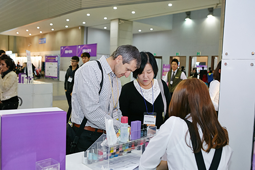 An international visitor inspects beauty products at K-Beauty Expo 2014.