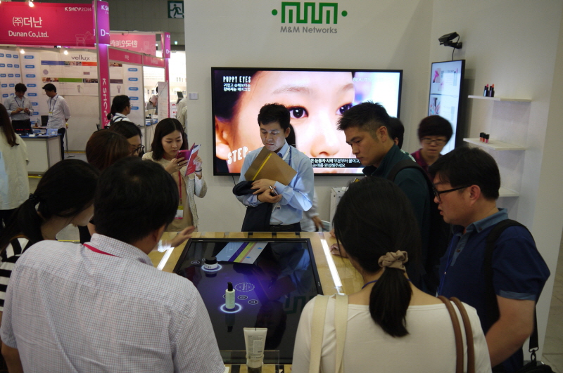 Visitors to M&M Networks' interactive table display booth watch a demonstration at the K Shop 2014.
