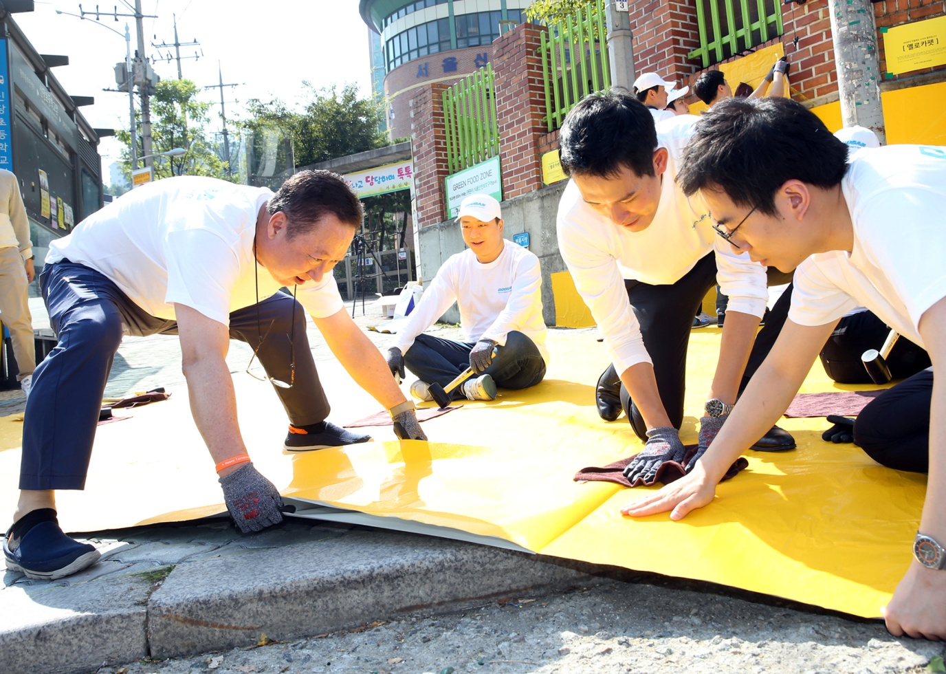 Park Yong-man, CEO of Doosan (middle), together with his employees, are affixing Yellow Carpet to a crosswalk with a hammer near Shin-dang elementary school in Jung-gu, Seoul.
