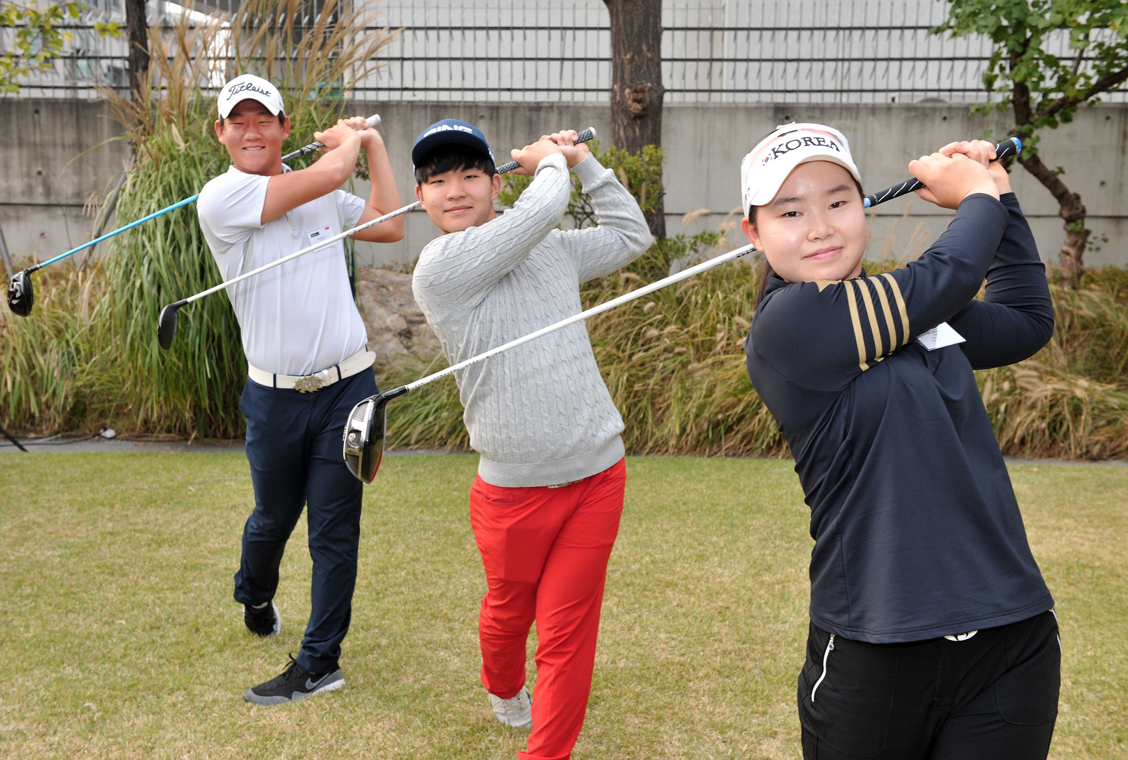 Three recipients of the Game On English-Golf scholarship take a golf swing for a photo shoot on Oct. 19 at the Embassy of New Zealand in Seoul. Golf scholarship recipients will participate in a new edu-sport program combining golf and English.
