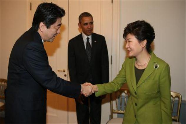 President Park Geun-hye shakes hands with Japanese Prime Minister Shinjo Abe while the U.S. President Barack Obama looks on during a Nuke Security Summit Meeting on March 26 (local time), 2014, in the Hague, the Netherlands.