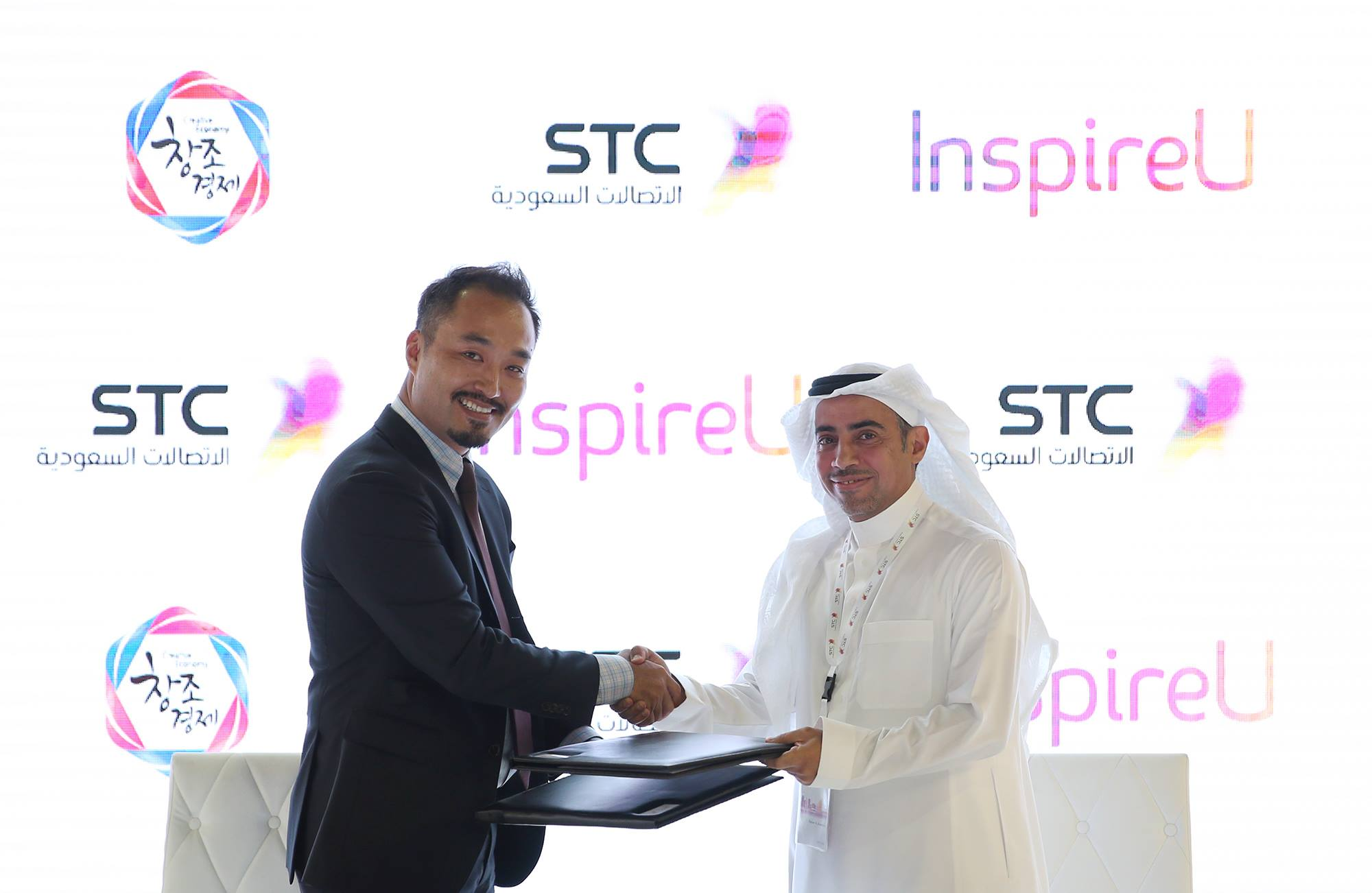 Representatives from the SK Group and Saudi Telecom Co. shake hands over a signed MOU between the two organizations.