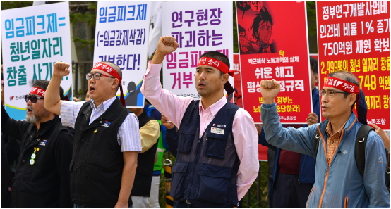 Workers of large businesses demonstrate against adoption of wage peak system.