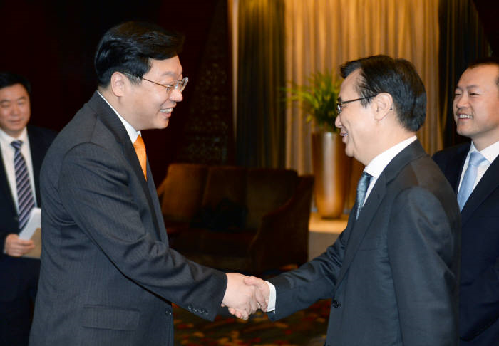 Joo Hyung-hwan (left), Korea's minister of industry, trade and resources is shaking hands with Chinese counterpart Gao Hucheng before a commerce minister meeting in Beijing, China on March 17.