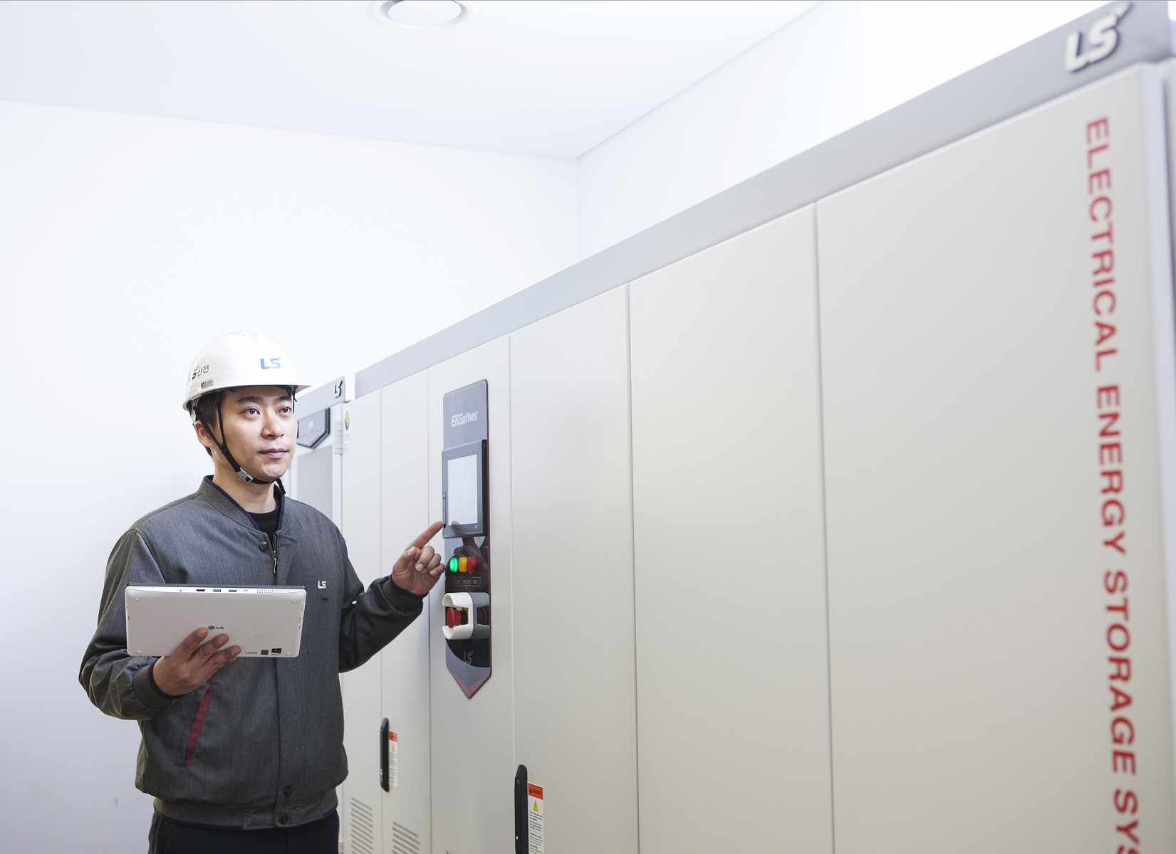 An LSIS employee inspects a power conditioning system (PCS) at a manufacturing facility