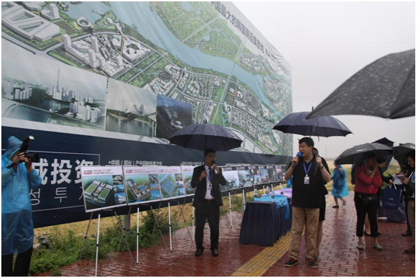 The personnel related to the China-South Korea Yantai Industrial Park introduce the plan for development of the industrial complex to the Korean press delegation amid a heavy rain.