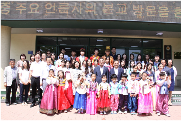 The Korean press delegation pose for a photographing with Kim Chang-eun, principal of Yantai Korean School, teachers and children who wear Hanbok, Korean traditional dress.