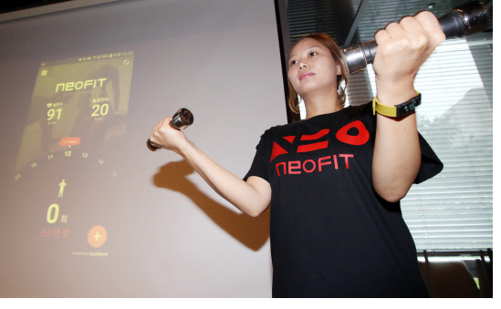 "A KT employee demonstrates KT's fitness band ""NeoFit"" at the KT future forum held at a restaurant in Centre Point Building in Gwanghwamun, Seoul, on August 25."
