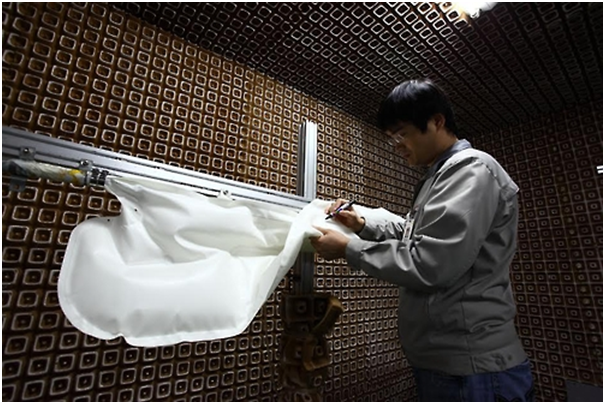A Kolon Industries employee is checking the quality of a side airbag.