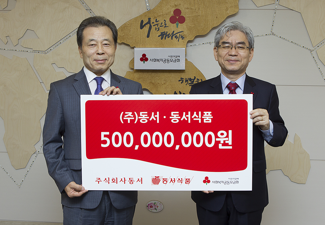 Kim Chang-soo, vice-president of Dongsuh Food (left) and Park Chan-bong (right) of the Community Chest of Korea pose for a photo shoot in the donation ceremony.