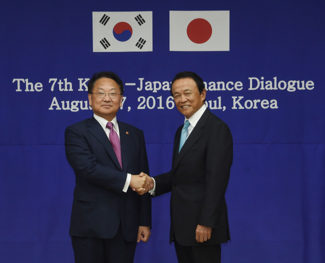 Finance Minister Yoo Il-ho and his Japanese counterpart Taro Aso pose at a finance minister meeting in Seoul on August 27 last year.