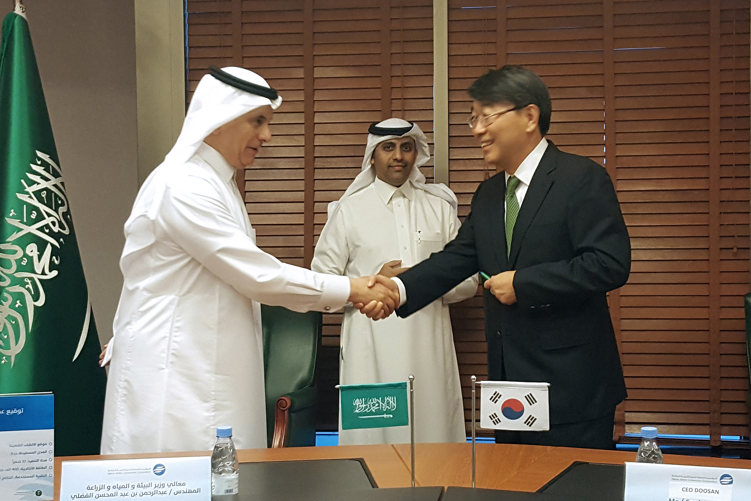 Yoon Seok-won (right), vice president of Doosan Heavy Industries, and Saudi Arabia's Minister of Environment Water and Agriculture shake hands after signing a seawater desalination plant construction deal in Saudi Arabia on March 28 (local time).
