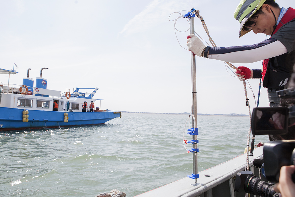 A joint team of SK Telecom and Hoseo University researchers installs a hydrophone to receive sound waves underwater in waters about 10 kilometers west of Incheon.