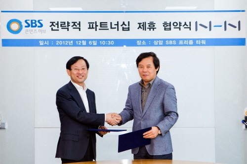 KimSang-heon, CEO of NHN (left) shakes hands with Hong Seong-chul, CEO of SBS Contents Hub after signing a strategic partnership for online broadcasting contents business on July 20.