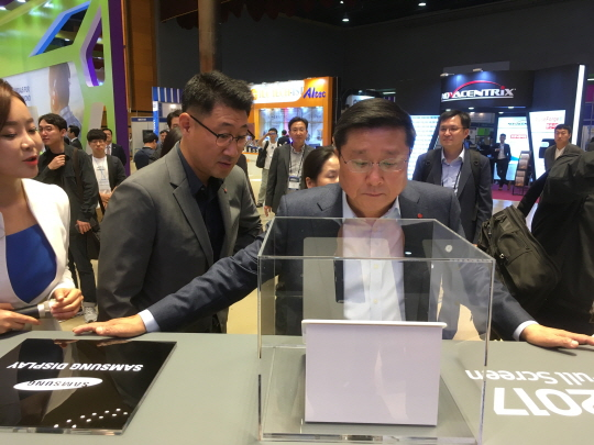 LG Display vice chairman Han Sang-beom is having a close look at devices of Samsung Display in the booth of the IMID held at COEX in Samsung-dong, Seoul on October 17.