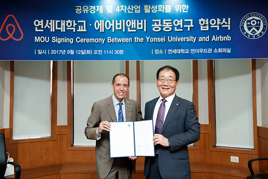 Christopher Lehane (L), Airbnb's head of global policy and public affairs, and Kim Yong-hak (R), president of Yonsei University, pose for a photo with the newly signed MOU between their two organizations.(photo courtesy: Airbnb)