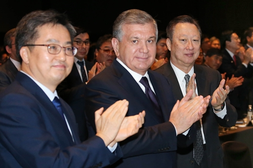 Economic deputy prime minister Kim Dong-yeon (left) claps with Uzbek President Shavkat Miromonovich Mirziyoyev (center) and Park Yong-man, chairman of the KCCI (right) at the Korea-Uzbek Business Forum held at the Shilla Hotel in Seoul on November 23.