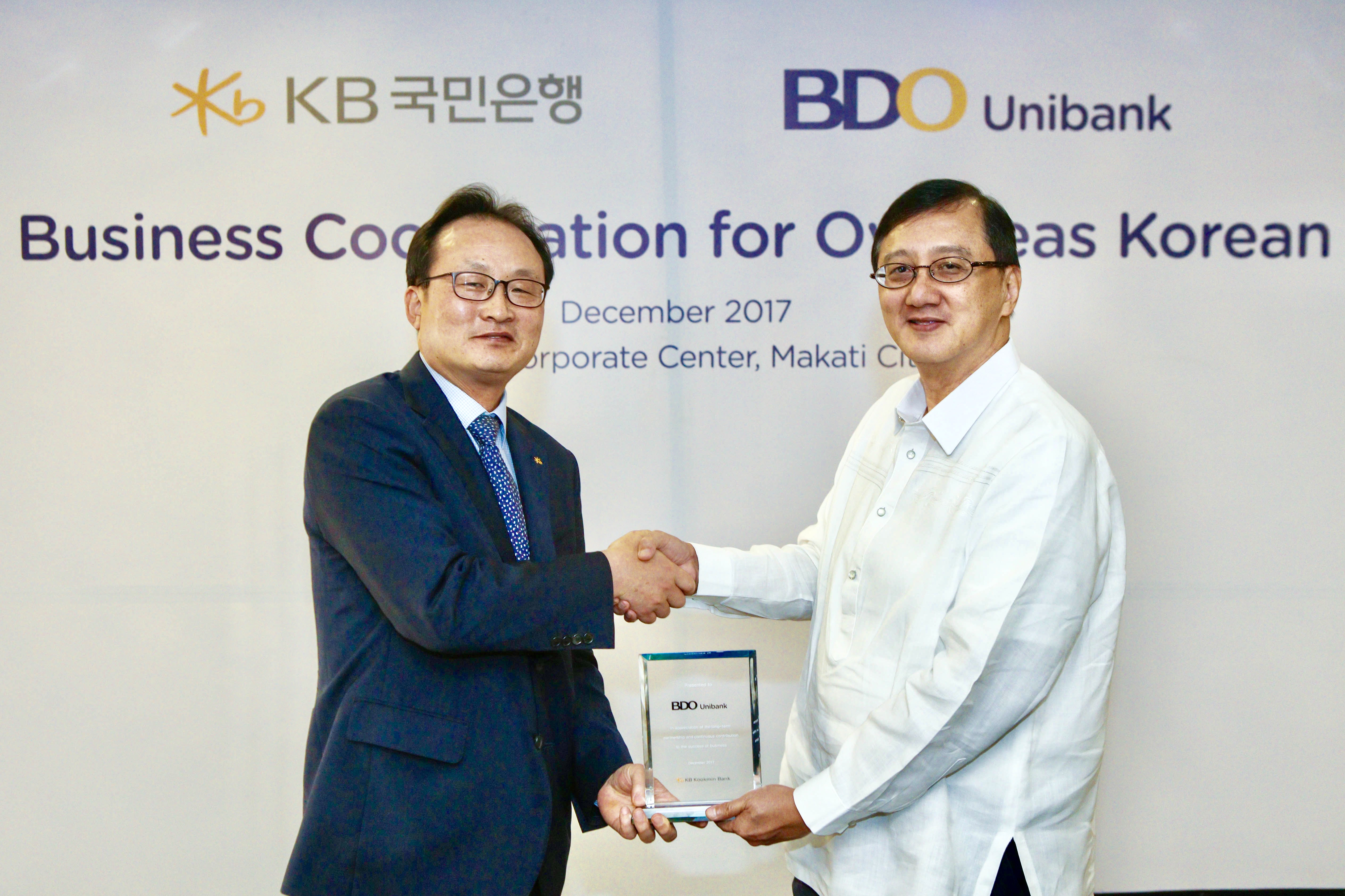 KB Kookmin Bank Lee Hwan-ju (left), head of the Foreign Exchange Business Division of KB Kookmin Bank pose with Edmundo Soriano, vice president of BDO Unibank after signing an agreement in the Philippines on Dec. 6.