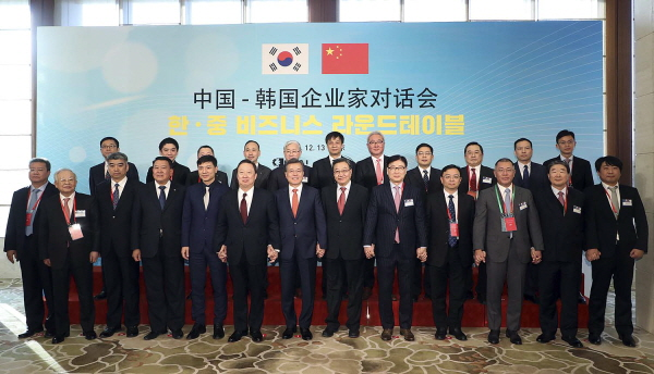 President Moon Jae-in (7th from left in front row) who visited China on a state visit is posing for a commemorative photo shoot hand in hand with other participants prior to the Korea-China Business Round Table in Beijing on December 13.
