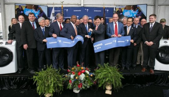 Kim Hyun-seok (sixth from left in front row), head of Samsung Electronics's CE Division is cutting a tape with Henry McMaster (fifth from left in front row), governor of South Carolina during a ceremony in Newberry, South Carolina, on January 12.