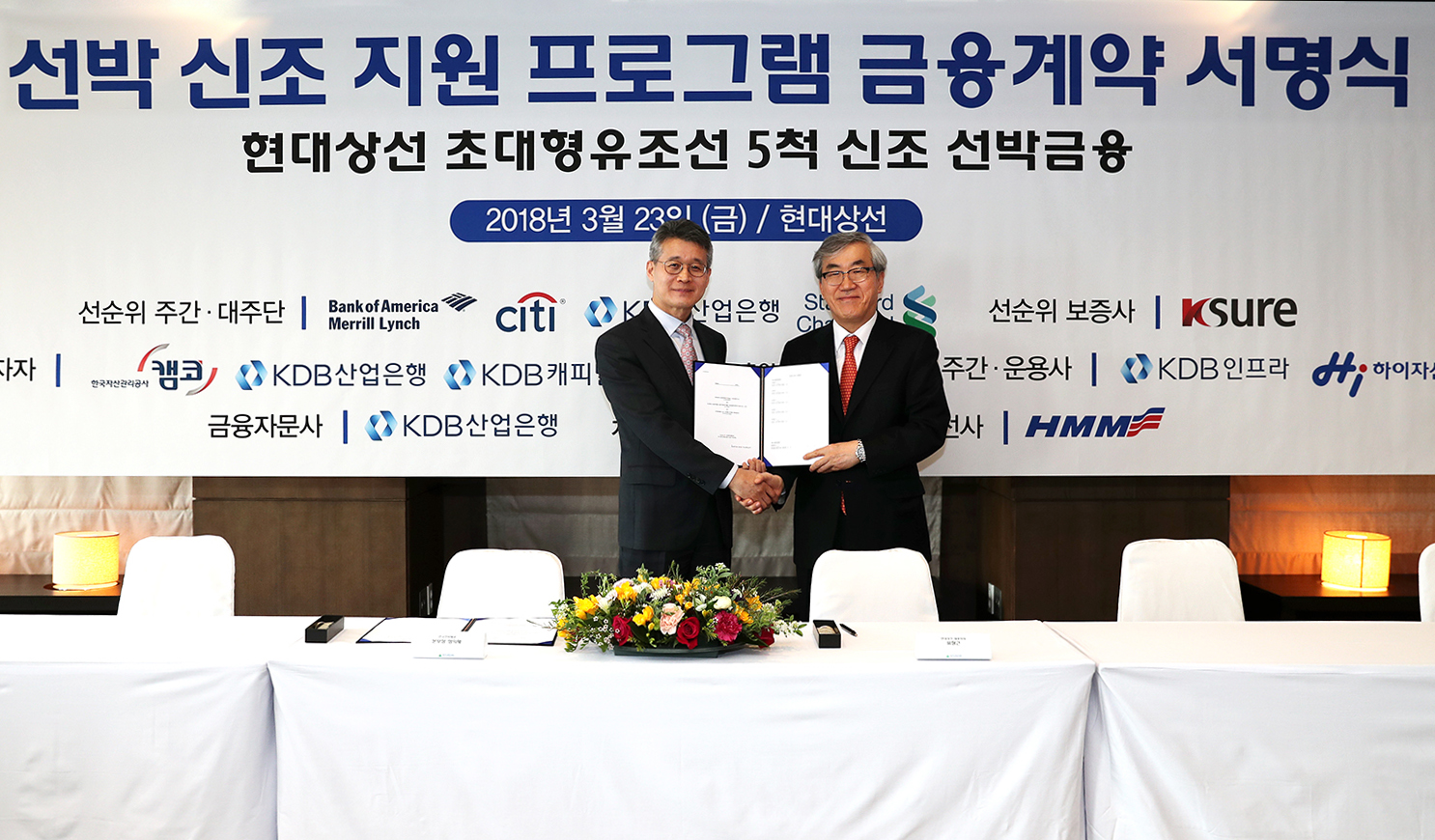 Hyundai Merchant Marine (HMM) CEO Yoo Chang-keun (right) and Jeong Ik-chae, director of Korea Shipping and Maritime Transportation, shake hands after signing a financial contract for new shipbuilding support at the HMM headquarters in Seoul on March 23.