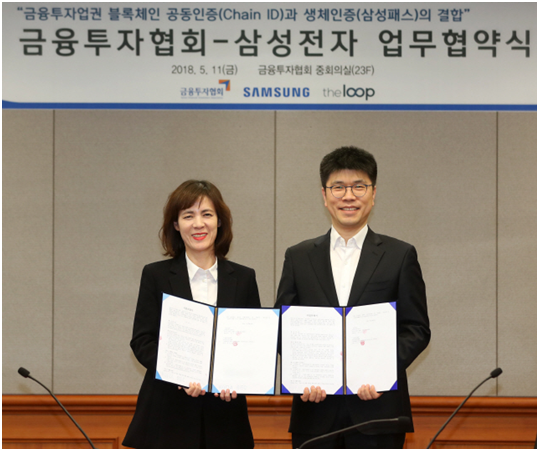 Kim Jung-ah, head of management innovation at Korea Financial Investment Association (KOFIA), left, and Kim Jung-sik, director of Samsung Electronics pose for a photo after signing an MOU for combination of Samsung Pass and Chain ID at the KOFIA headquarters in Yeouido, Seoul, on May 11