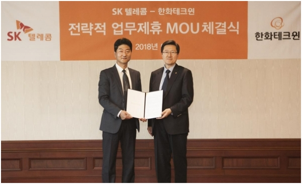 Jung Soon-koo (left), head of the Security Business Unit at SK Telecom, and Ahn Soon-hong, head of the Marketing Office at Hanwha Techwin, pose for a photo shoot after signing a business agreement on May 29.