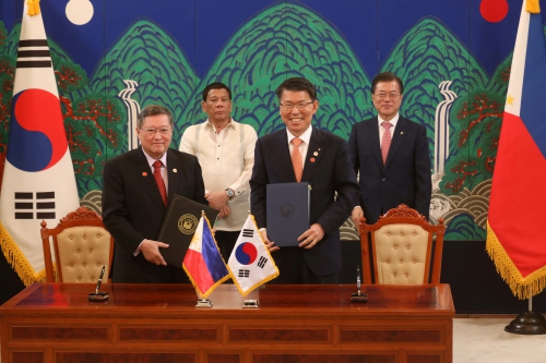 Eun Sung-soo (right, front row), president of the Export-Import Bank of Korea, and Carlos Dominguez, secretary of finance of the Philippines, pose for a photo after signing a loan agreement at the Blue House on June 4 in the presence of President Moon Jae-in (right,) and Rodrigo Duterte, president of the Philippines